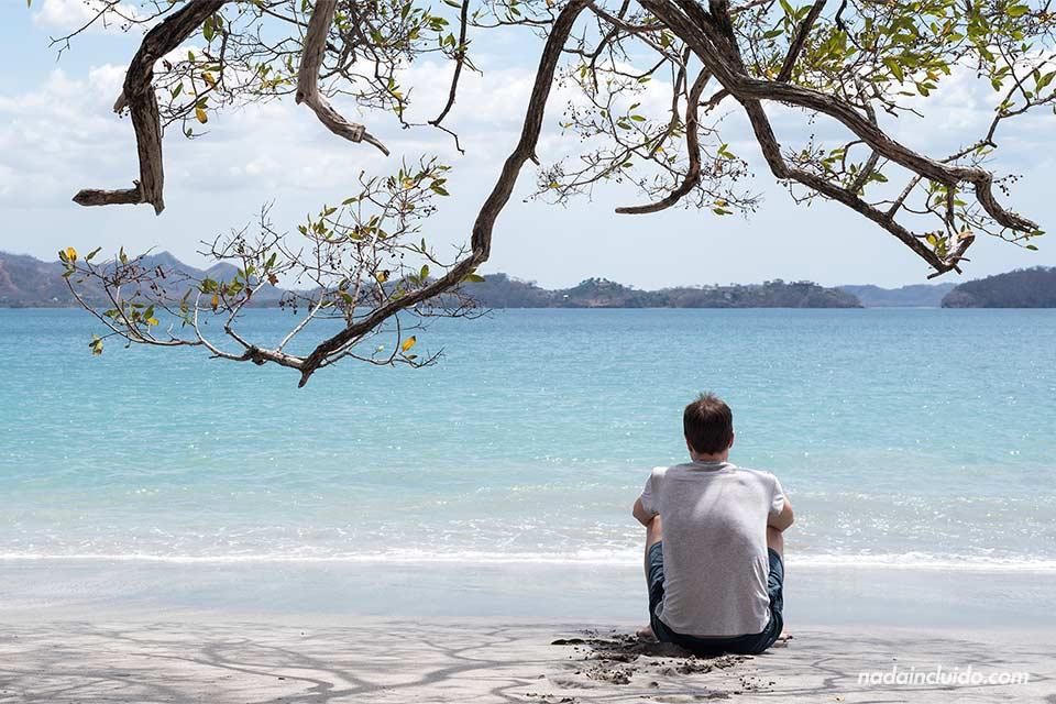 Sentado en la arena de Playa Dantita, en Guanacaste (Costa Rica)