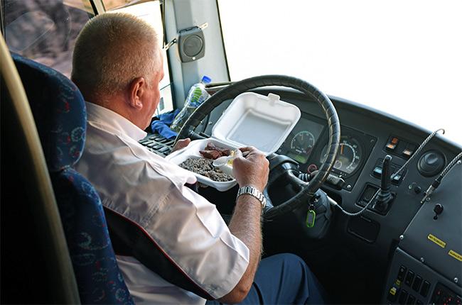Chófer comiendo mientras conduce el autobús de la ruta Costa Rica - Nicaragua