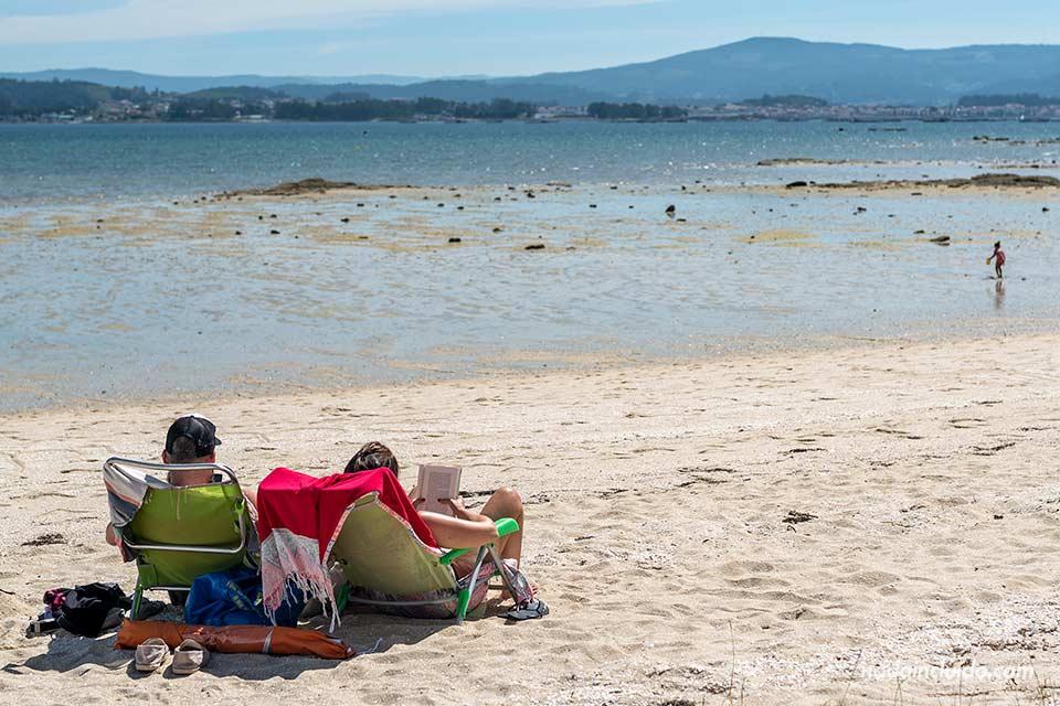 Pareja en la playa de Xastelas en el parque natural de Carreirón (Illa de Arousa, Galicia)
