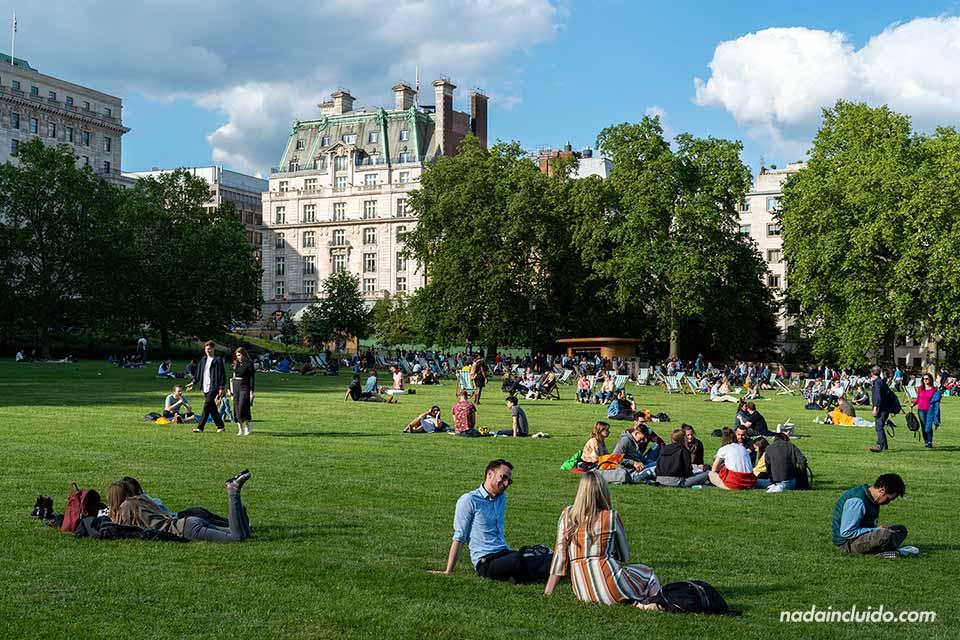 Locales y turistas se relajan en un parque de Londres (Inglaterra)