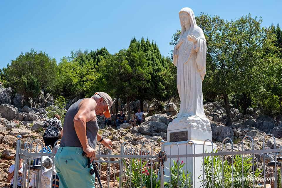 Anciano rezando frente a la estatua de La Virgen en el Monte de las Apariciones de Medugorje (Bosnia)