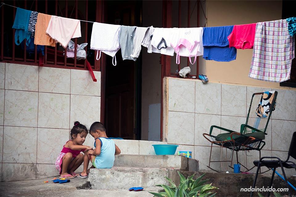Dos niños costarricenses juegan en la puerta de su casa, en Quepos (Costa Rica)