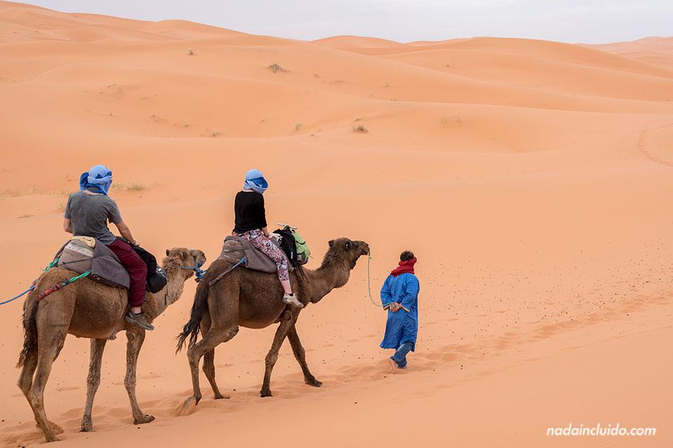 Dos turistas en camello por el desierto del Sáhara (Marruecos)