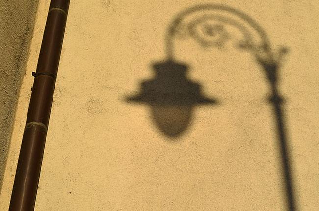 Sombra de una farola en una fachada del centro histórico de Sibiu (Rumanía)