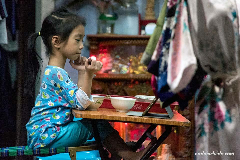 Niña come en la puerta de su casa en Hoi An, Vietnam