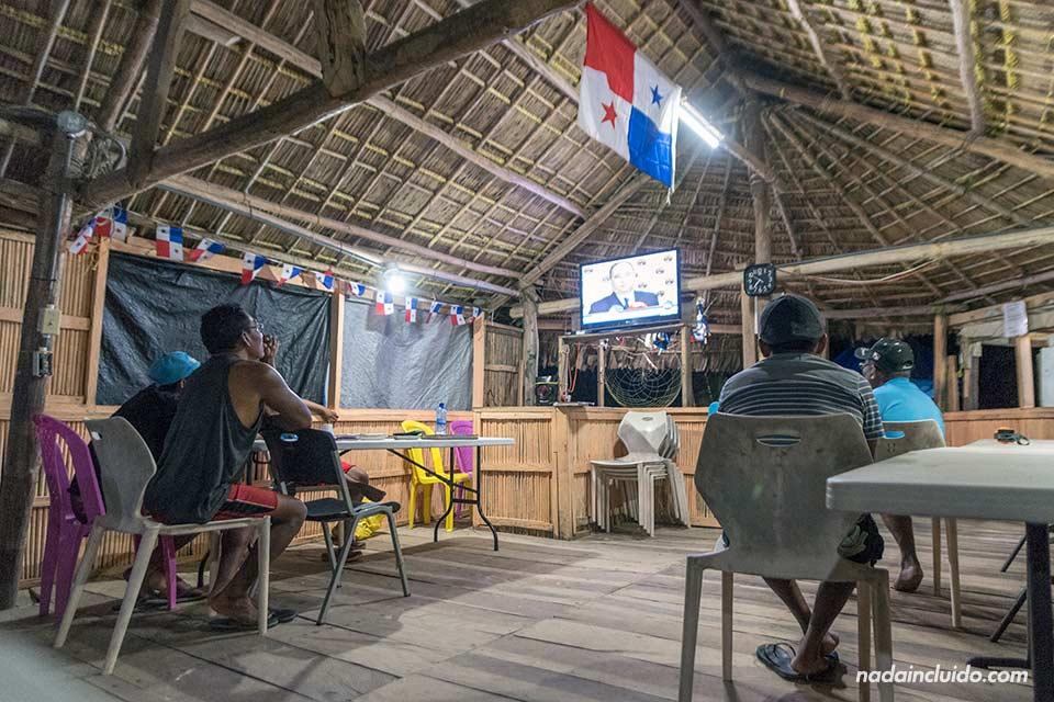 Un grupo de Guna Yala ven la televisión en el único bar de Isla Perro Chico, en el archipiélago de San Blas (Panamá)