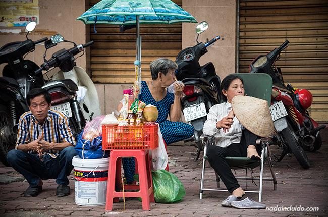 Tres vietnamitas en un puesto de venta en las calles de Ho Chi Minh (Vietnam)
