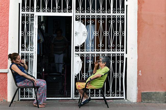 Lugareños en la puerta de una tienda de ropa en la calle de la Libertad de Granada (Nicaragua)