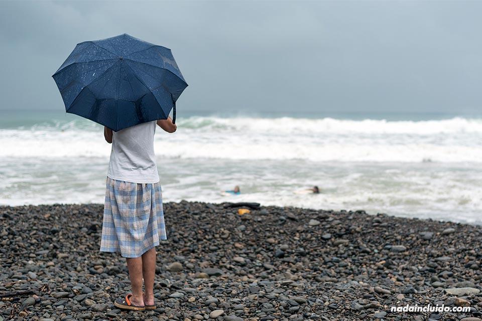 Una mujer se tapa con un paraguas de la lluvia en la playa Dominical (Costa Rica)