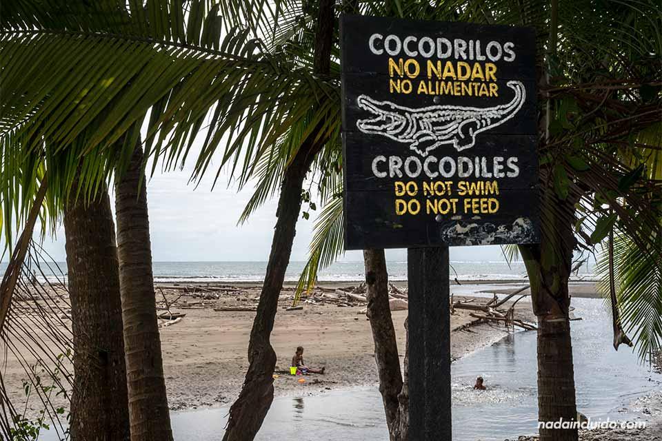 Niños juegan en el agua junto a un cartel que avisa del peligro de cocodrilos en el río (playa Uvita, Costa Rica)