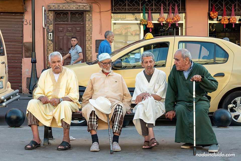 Marroquíes sentados en un banco de Marrakech (Marruecos)