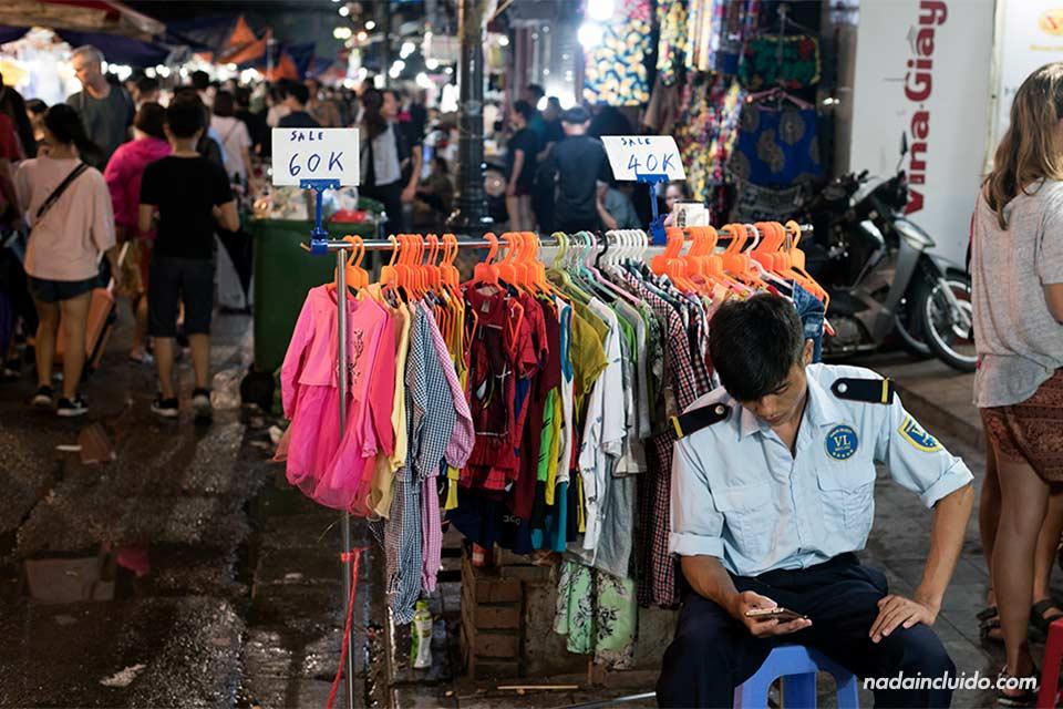 Un agente de seguridad mira el móvil en el Night Street Market de Hanoi (Vietnam)