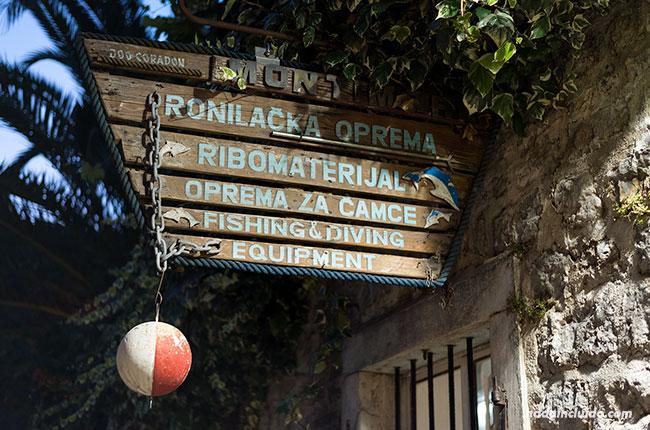 Un cartel de una tienda iluminado en el Stari Grad de Budva (Montenegro)