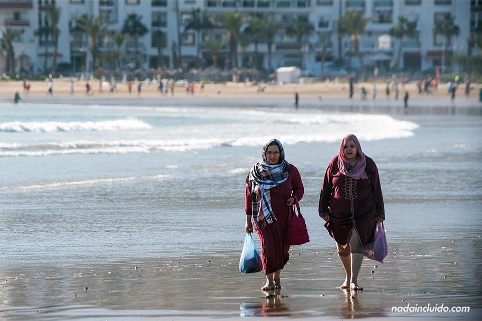 Mujeres marroquís pasean por la playa de Agadir (Marruecos)