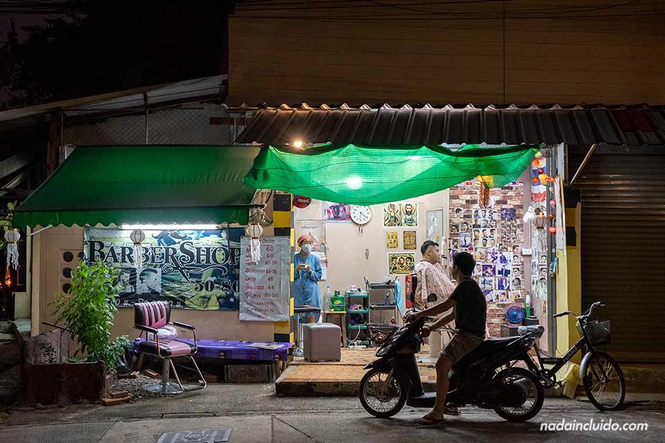 Iluminación nocturna de una pequeña peluquería en Chiang Mai (Tailandia)