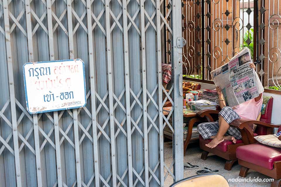 Una lugareña lee el periódico en su casa de Chiang Mai (Tailandia)