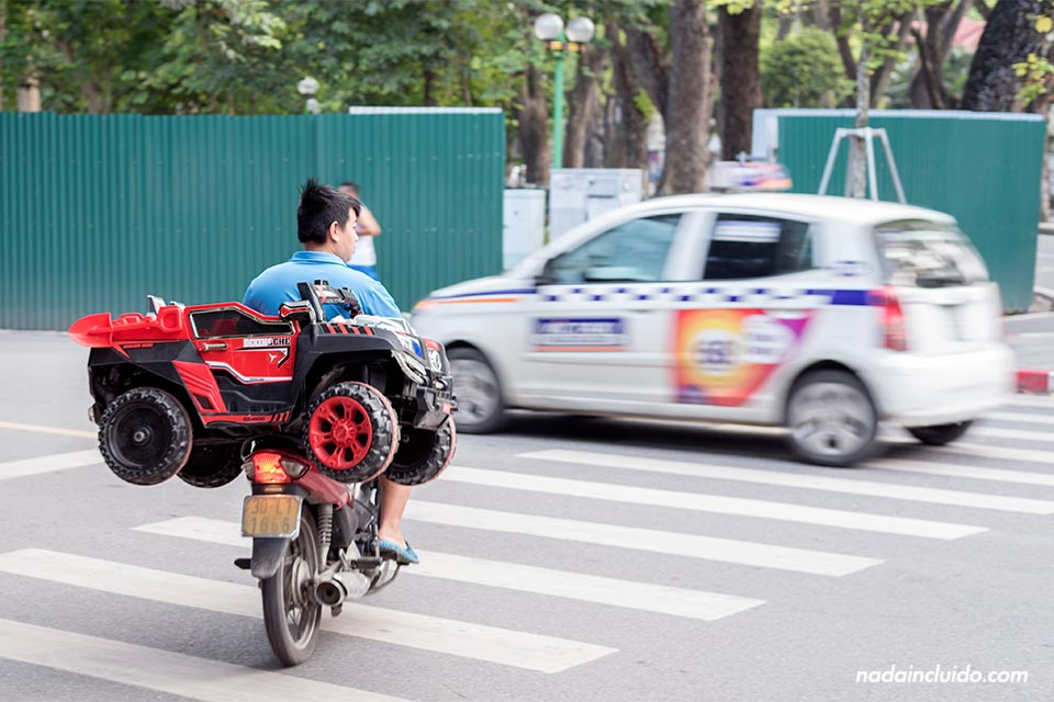 Moto transporta un coche de juguete en Hanoi (Vietnam)