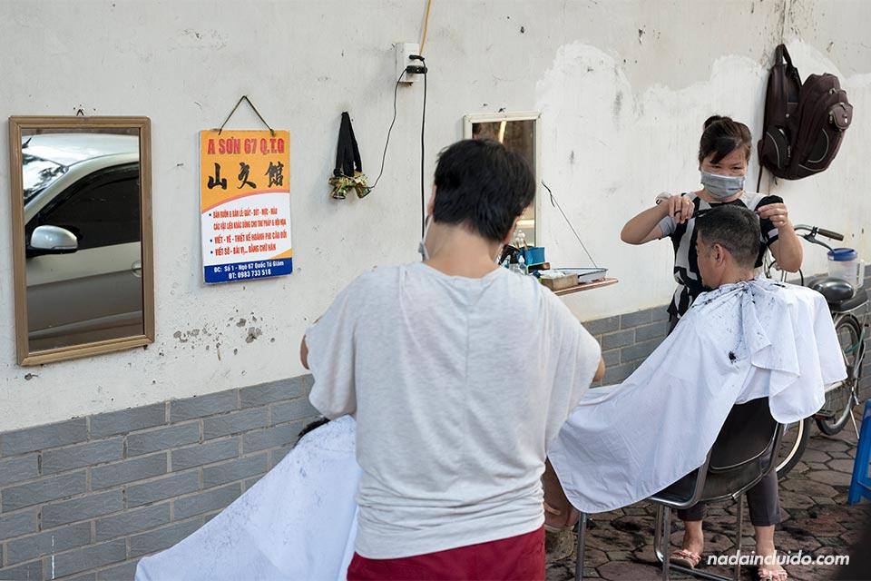Vietnamitas se cortan el pelo en una peluquería callejera de Hanoi (Vietnam)