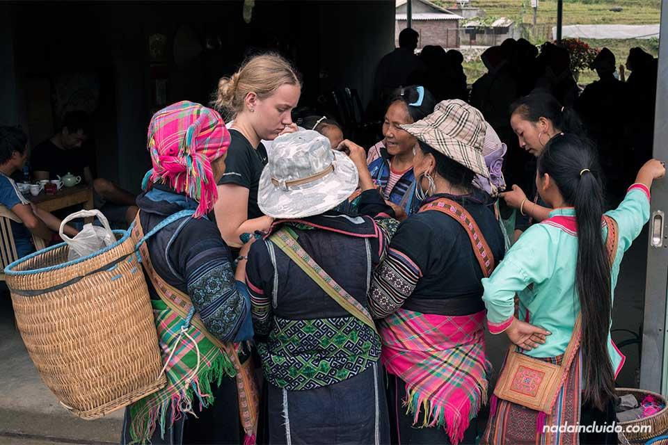 Turista compra rodeado de mujeres Hmong en la aldea de Lao Chai, Vietnam