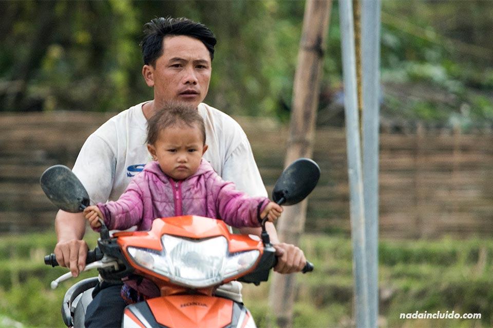 Niñas pequeña pasea en moto junto a su padre en la aldea de Lao Chai (Vietnam)