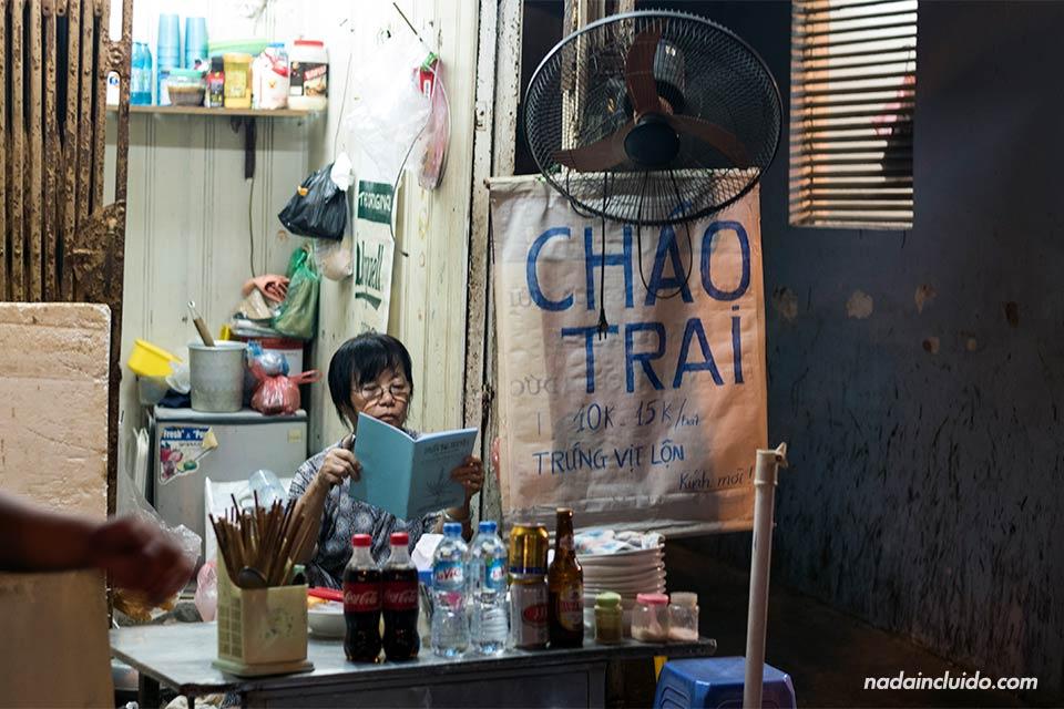 Vietnamita lee un libro en las calles de Hanoi (Vietnam)