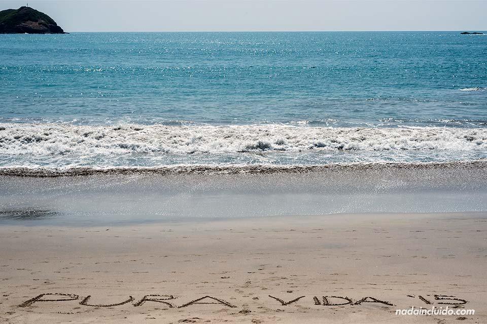 Pura Vida escrito en la arena de la Playa Espadilla Sur en el Parque Nacional de Manuel Antonio (Costa Rica)