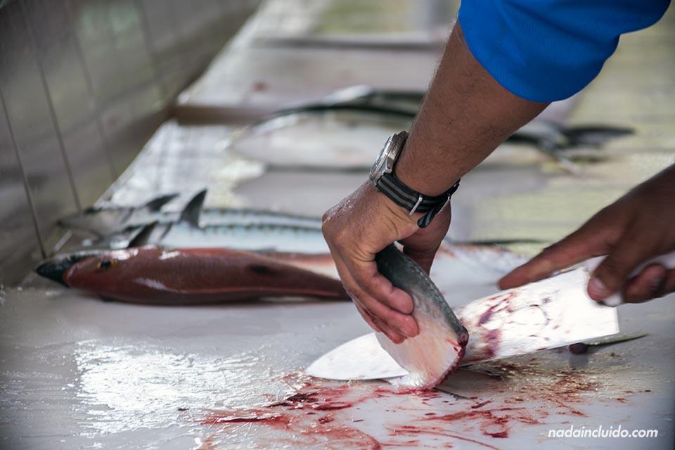 Pescador cortando un pez en Mal País (Costa Rica)