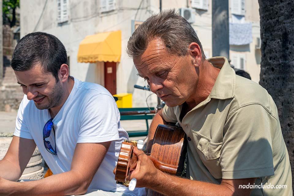 Músico callejero toca la guitarra en el Stari Grad de Perast (Montenegro)