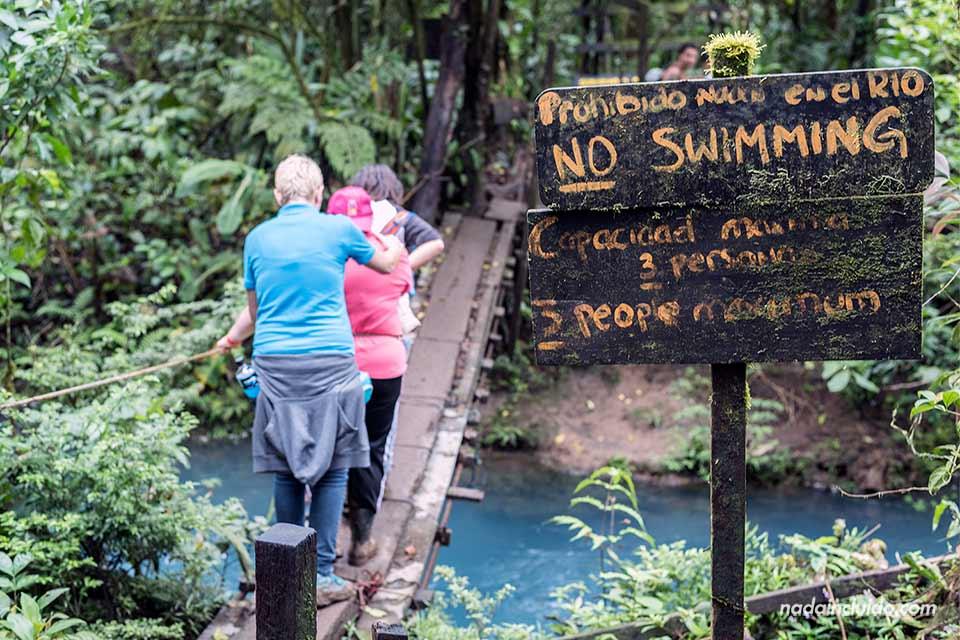 Un grupo de turistas cruzan un estrecho puente colgante en Río Celeste, en el Parque Nacional del Volcán Tenorio (Costa Rica)