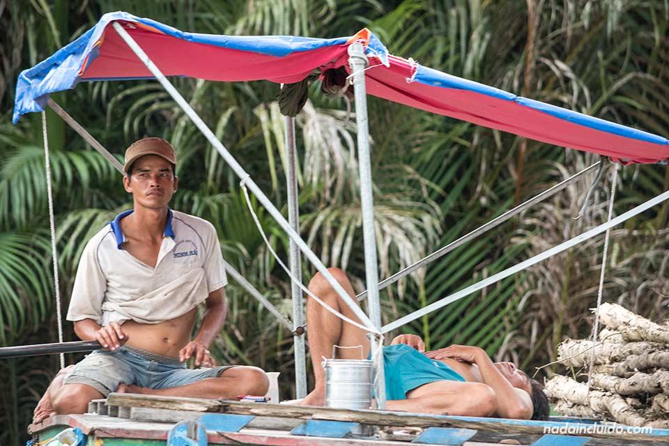 Vietnamitas descansan en su barco en el delta del Mekong (Vietnam)