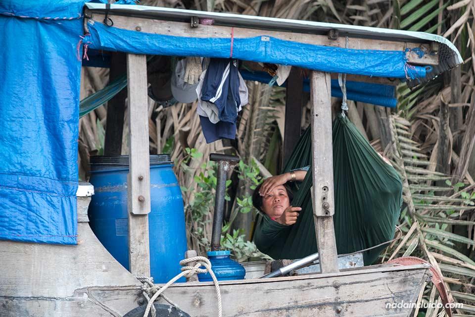 Mujer descansa en un barco vietnamita sobre el río Saigón (Vietnam)