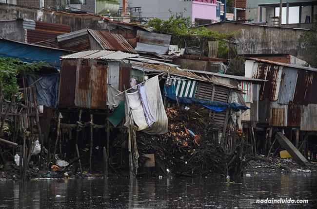 Basura y casas destrozadas sobre el río Saigón (Vietnam)