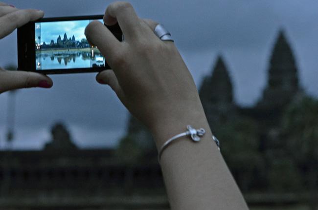 Un turista hace una fotografía con el móvil en Angkor Wat (Siem Reap, Camboya)