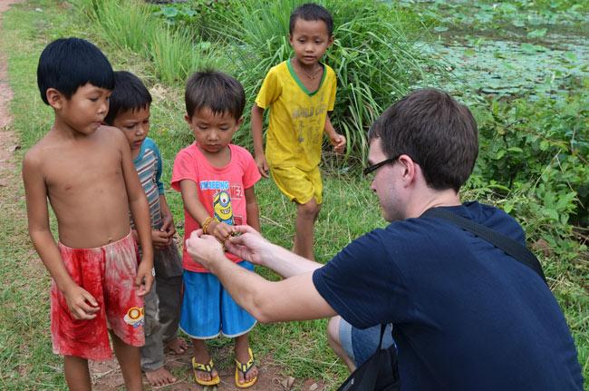 Regalando una cinta de la virgen del Pilar en una aldea necesitada de Camboya