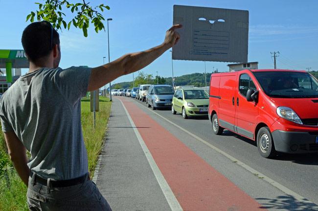 Un autoestopista llama a la suerte en una carreta con mucho tráfico