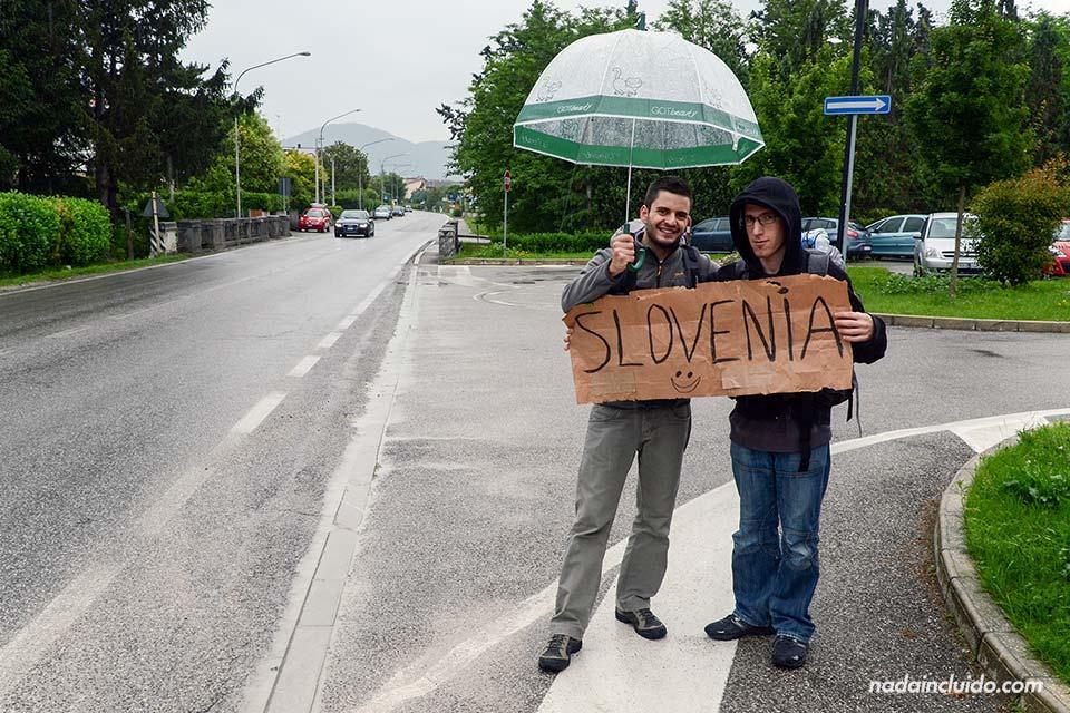 Dos mochileros haciendo Autostop en la frontera entre Italia y Eslovenia