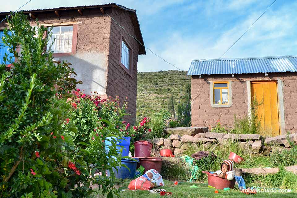 Un niño juega en el jardín de su casa en Llachón, un pueblo junto al Lago Titicaca (Perú)