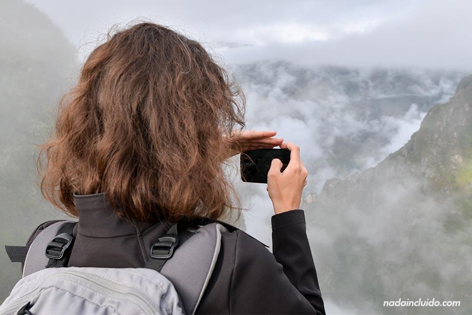 Una turista haciendo fotos con el móvil desde lo alto del Machu Picchu