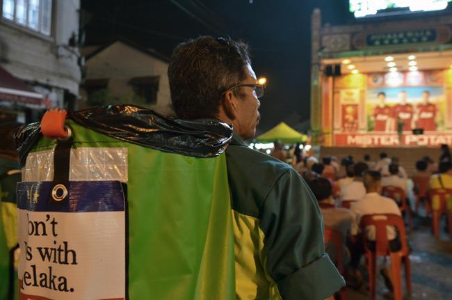 Un hombre con una papelera a la espaldas en Jonker Street (Malaca, Malasia)