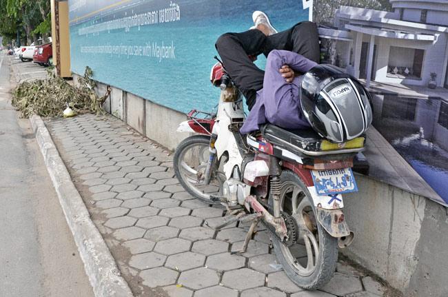 Un camboyano duerme sobre su moto (Phnom Penh, Camboya)