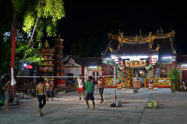 Jóvenes jugando a volleyball en Phuket Town (Tailandia) junto a un templo chino